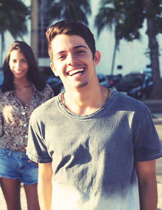 Young man and woman smiling outdoors